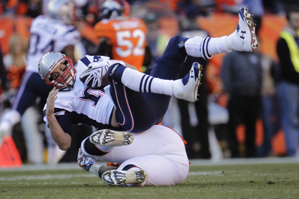 Patriots quarterback Tom Brady is sacked by Broncos defensive end Robert Ayers in the second half Sunday's AFC championship game at Denver.