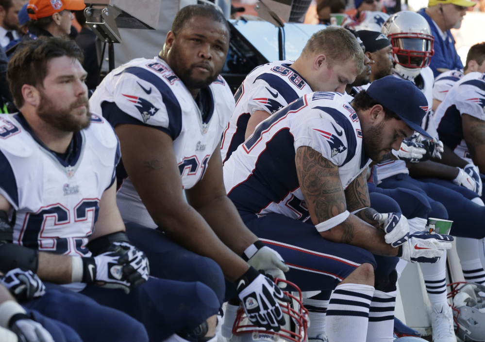 Patriots players on the bench watch the closing minutes of the AFC championship game Sunday at Denver. The Broncos won 26-16 to advance to the Super Bowl.