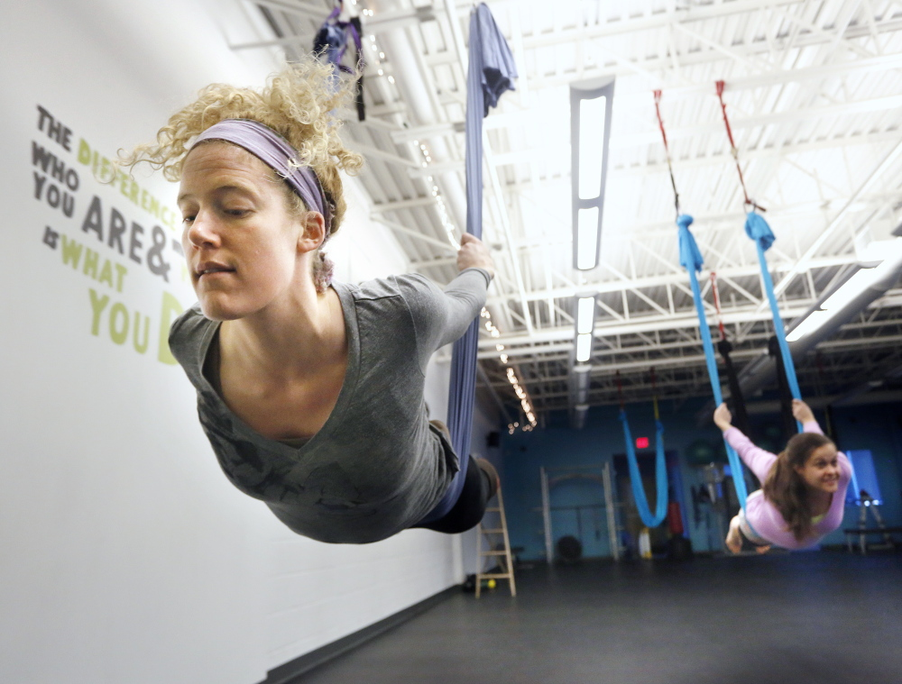 Kathleen Jones of Freeport, left, and Amy Case of Portland get in the swing of performing aerial yoga poses during a class at Zone 3 Fitness in Scarborough on Sunday.