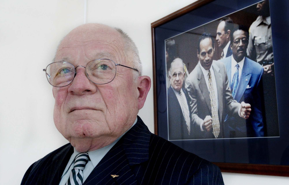 F. Lee Bailey poses next to a photo of O.J. Simpson as he reacts after the court clerk announced that Simpson was found not guilty of the murders of Nicole Brown Simpson and Ronald Goldman.