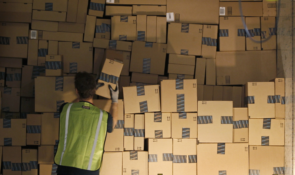 A worker stacks a shipping trailer with boxed items for delivery at Amazon's distribution center in Phoenix in November. Amazon has changed the face of retail shopping, New York convention speakers said.