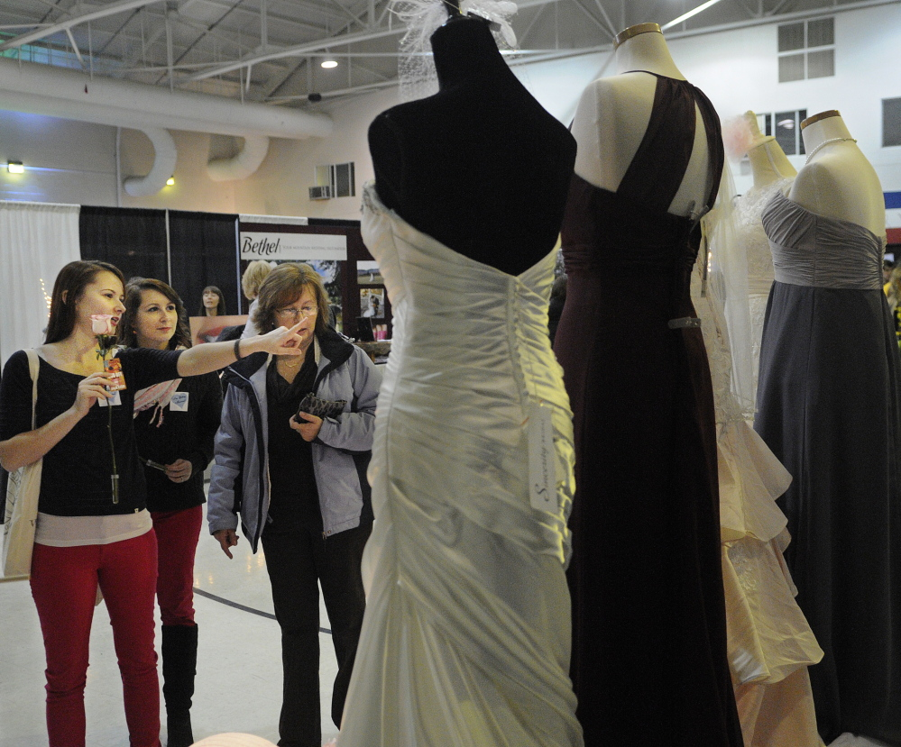 Chantelle Osgood, left, her sister, Jenna Osgood, and mother, Lori Osgood, inspect wedding gowns on display at the Hussey's General Store's booth at the 22nd annual wedding show in Augusta on Sunday. Both daughters are getting married.