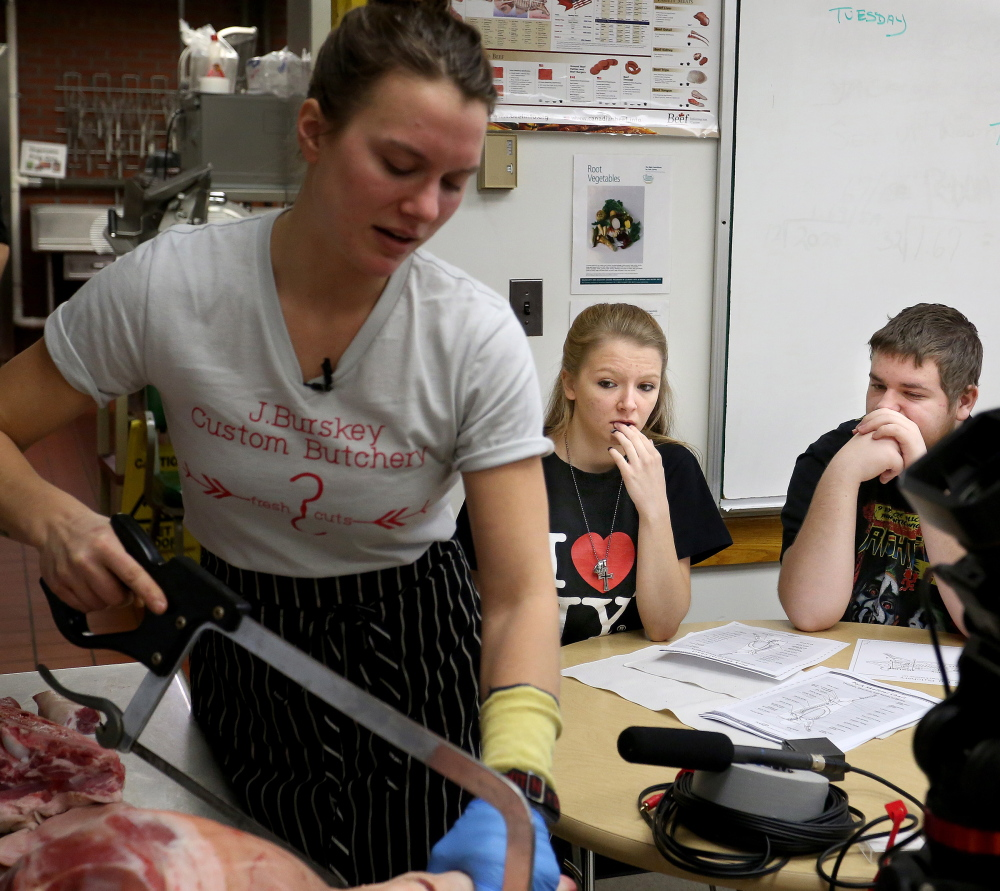 Jaclyn Burskey, 25, of Montpelier, Vt., butchers portions of a pig as Haley Bean, 17, of Bonny Eagle, and Jacob Hamer, 17, of Wells, watch the farm-to-table demonstration Tuesday during a culinary arts class at Portland Arts and Technology High School. At top, some of the chops that resulted from Burskey's work.