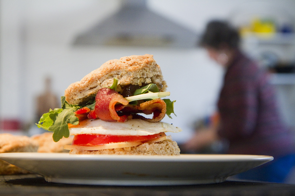 One of Stacy Cooper's sandwiches consists of a halved biscuit with smoked cheddar cheese, nitrate-free bacon, an over-easy egg, spiced tomato jam and arugula.