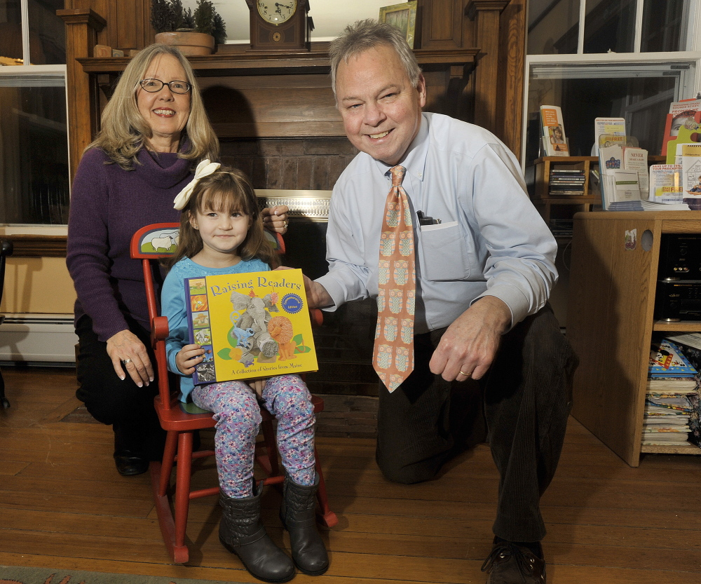 "Giovanna ""Gigi"" Bella, 5, of York receives Raising Readers' 2 millionth book from Dr. Stephen Brennan and his office manager, Kathy Mackey, at his practice in York on Wednesday. The statewide network has been giving books to children since 2000."