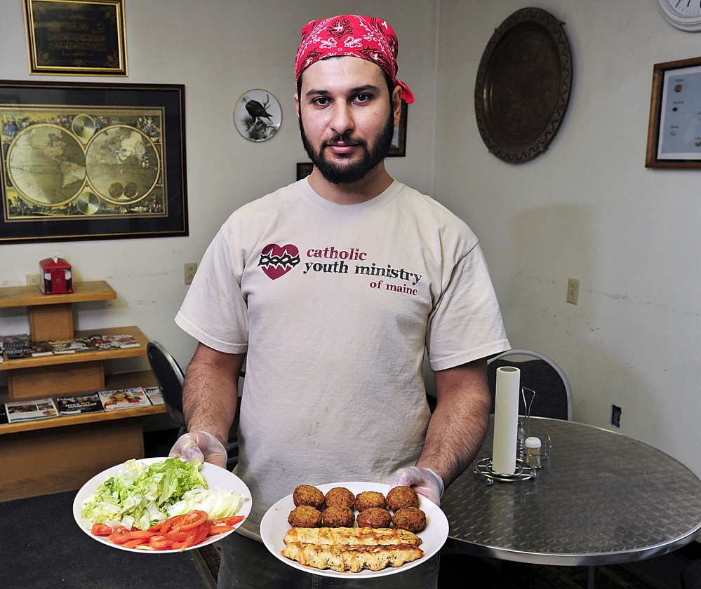 Ahmed Abbas with a salad and a falafel and chicken kabab plate at his Tenur Bread in Portland.