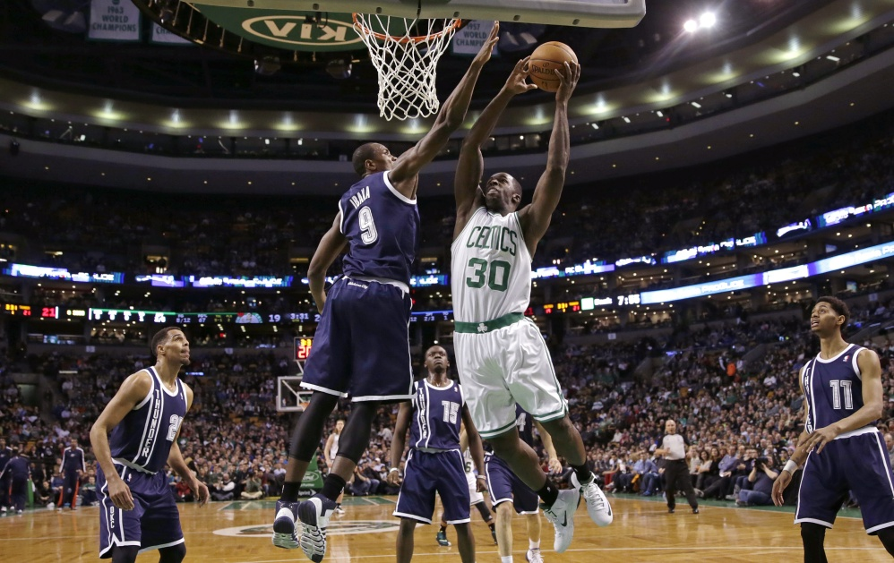 Boston Celtics forward Brandon Bass (30) drives to the basket against Oklahoma City Thunder forward Serge Ibaka (9) during the first half of an NBA basketball game in Boston, Friday, Jan. 24, 2014.