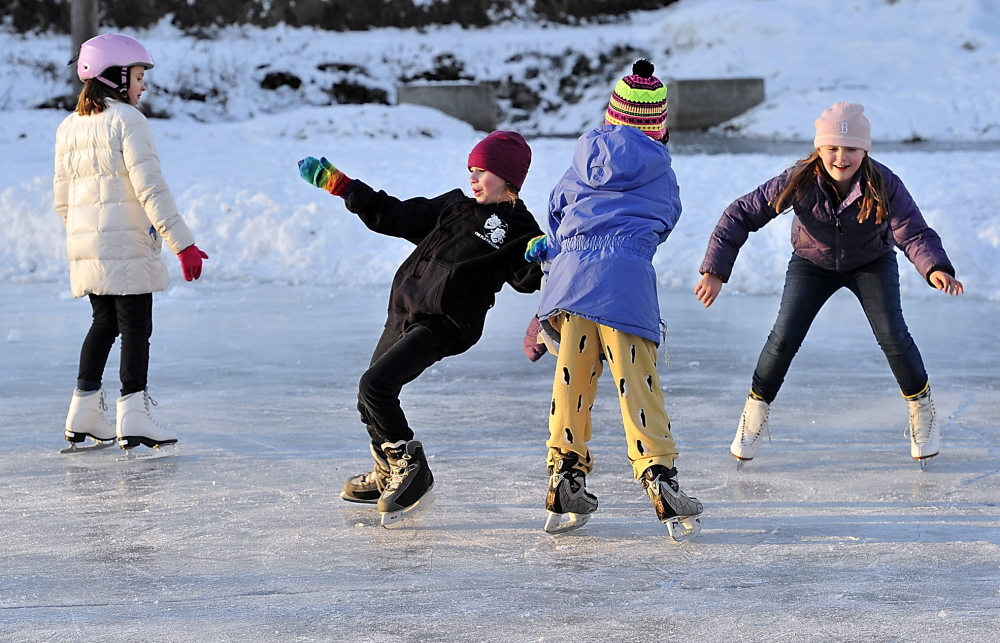 Lexi Inger, 9, gets help with her balance from Ari Rustad-Rogers, 10, as Cassie Watt, 9, left, and Eliza Burgmaier, 10, right, work on their skating skills on Friday at the Orland Blake Skating Pond in Yarmouth.