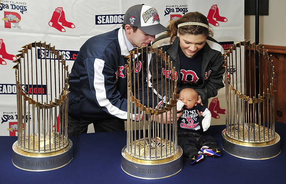 Devan Knight, left, and Ashli Canabush of Lisbon Falls sit their 2-week-old baby, Brayden, among the three World Series trophies for a photo Saturday at Hadlock Field. Many fans at Hadlock, then at L.L. Bean, waited for the exact same opportunity to remember the Red Sox season.