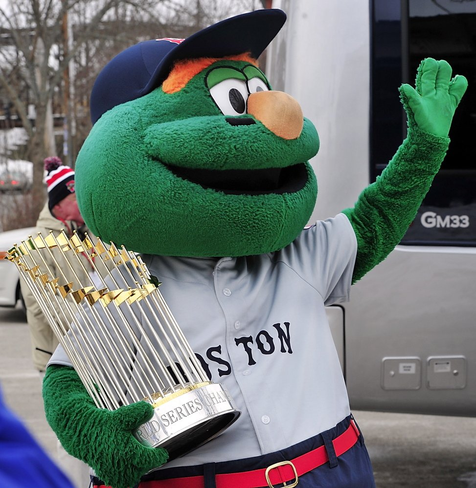 Wally, the Boston Red Sox mascot, waves with the 2013 World Series trophy – the first of the three that were taken off a bus and later displayed at Hadlock Field. The trophies later appeared in Freeport, and will be in Bangor and Orono on Sunday.