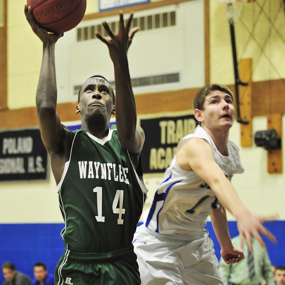 Serge Nyirikamba, who finished with 19 points and 14 rebounds for Waynflete, finds room inside against Zach Seamans of Old Orchard Beach to score Saturday during the Flyers' 72-43 victory.