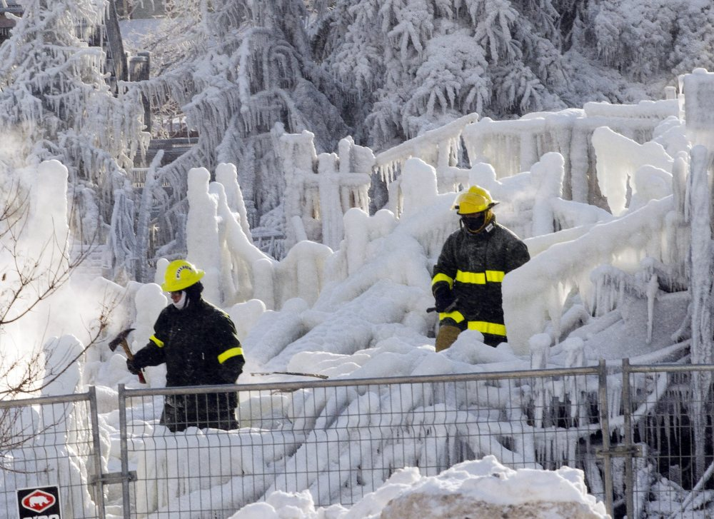 Rescue personnel search on Friday through the icy rubble of fire that destroyed a seniors' residence in L'Isle-Verte, Quebec. The search was temporarily called off Sunday because of frigid temperatures.