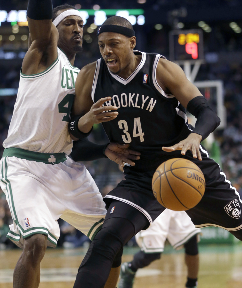 Brooklyn's Paul Pierce drives past the man the Nets traded to Boston in last summer's blockbuster deal, Gerald Wallace, during the Nets' 85-79 victory Sunday.