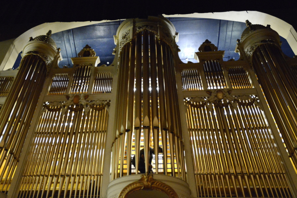 Behind the pipes, Nick Wallace works Monday on a section of the Kotzschmar Organ being reinstalled in Merrill Auditorium.