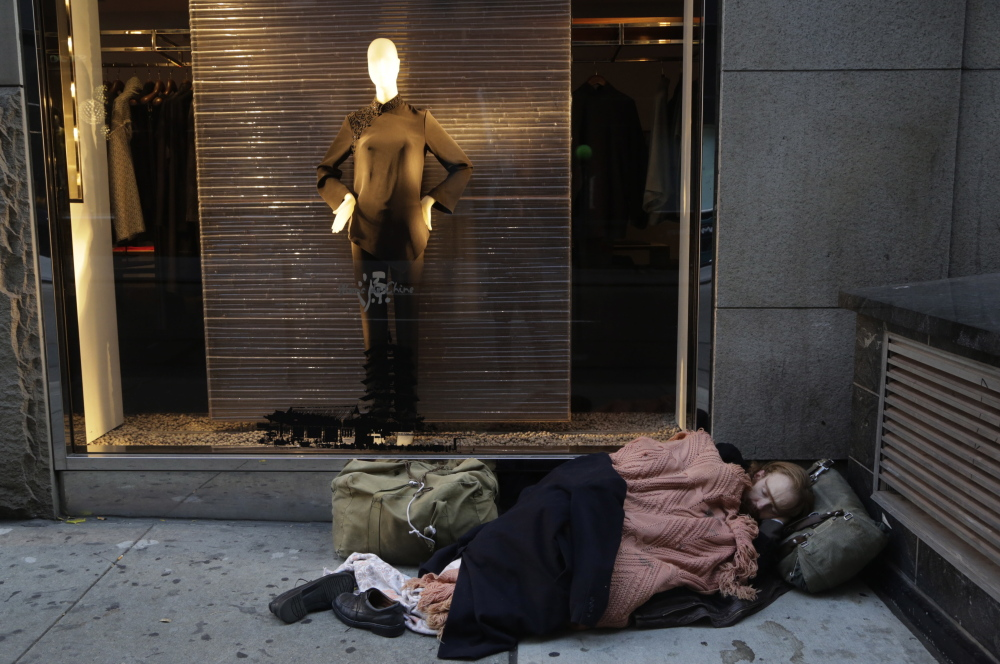 A man sleeps on the sidewalk outside Blanc de Chine, a high-end store in New York. From the White House to the Vatican to the business elite in Davos, Switzerland, the issue of income inequality is attracting attraction.