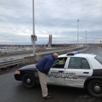 John Patriquin/Staff Photographer One drawbridge leaf of the Casco Bay Bridge can be seen stuck in the open position in the background as a Portland Police Department cruiser blocks southbound traffic Monday afternoon.