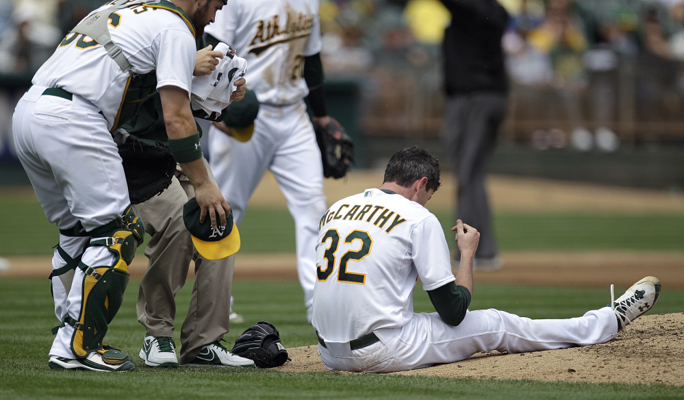 In this Sept. 5, 2012, file photo, Oakland Athletics catcher Derek Norris, left, comes to the aid of pitcher Brandon McCarthy (32) who was hit in the head by a ball hit by Los Angeles Angels' Erick Aybar in the fourth inning. Major League Baseball has approved a protective cap for pitchers, hoping to reduce the effects of being hit in the head by line drives.