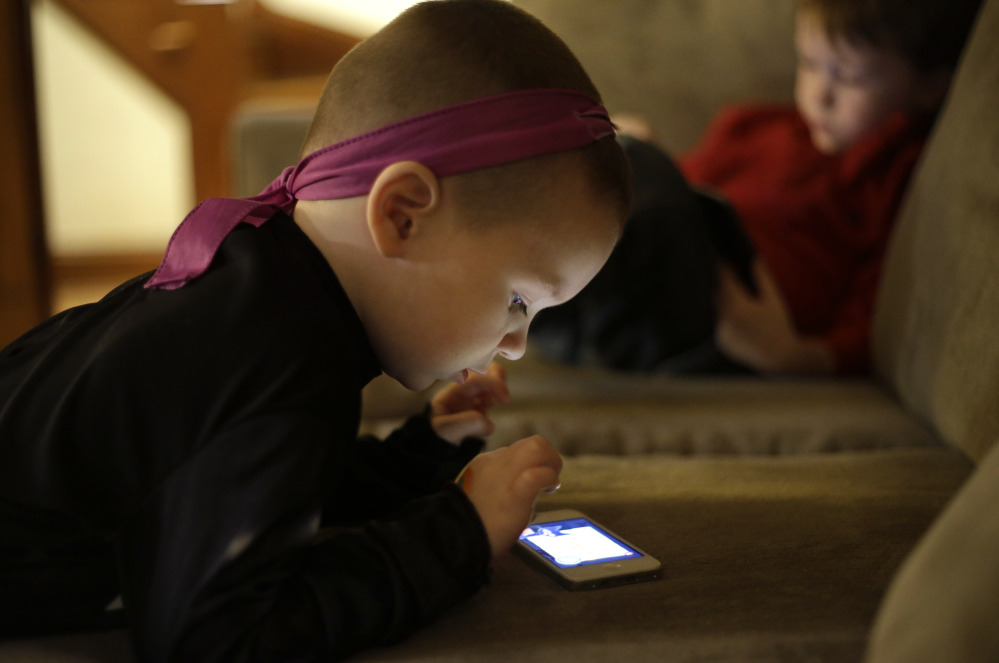 Nolan Young, 3, looks at a smart phone while his brother Jameson, 4, right, looks at a smart tablet at their home in Boston on Monday.