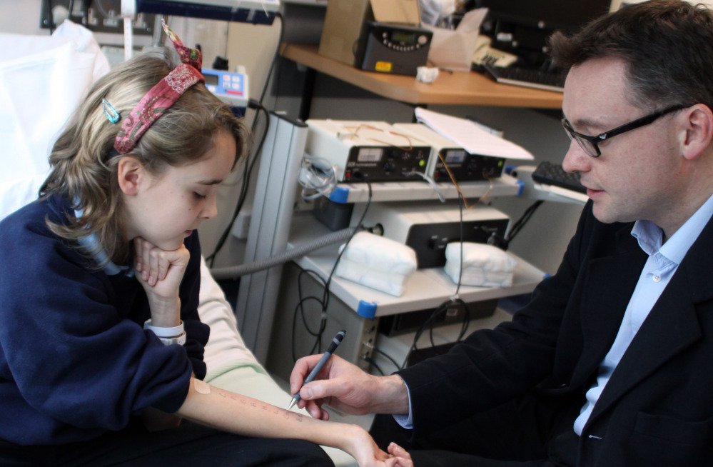 Dr. Andrew Clark performs a skin prick test used to diagnose food allergies on Lena Barden, 12, in Cambridge, England.