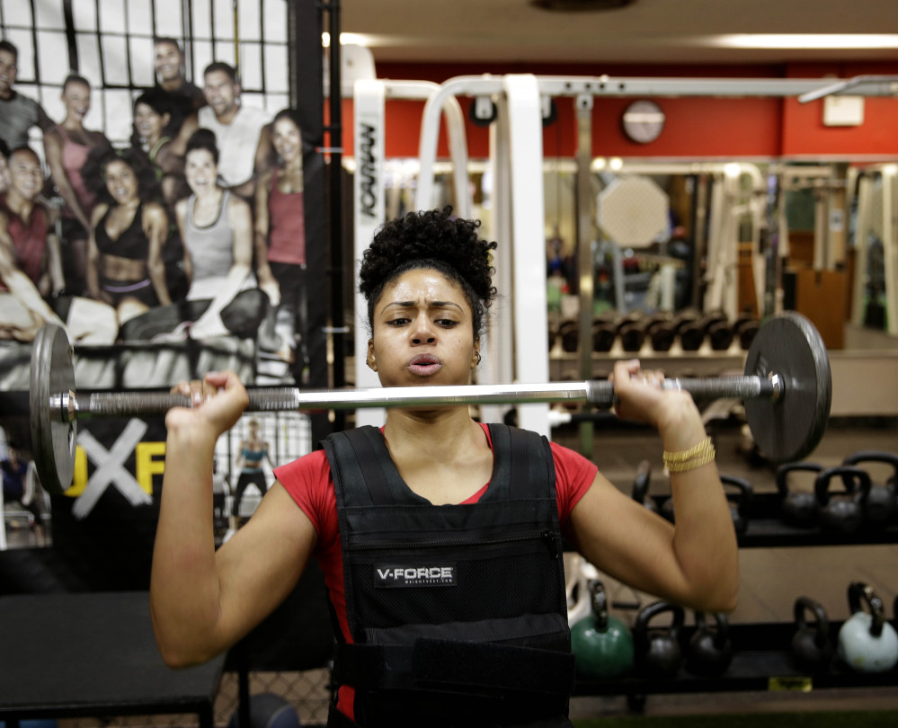 Hildany Santana lifts weights during an exercise session in New York. Santana is training to become one of the few female firefighters in the New York City Fire Department.