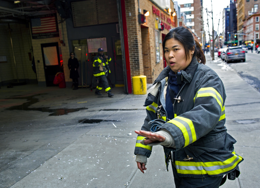 New York City firefighter Sarinya Srisakul holds back pedestrians so a firetruck can exit a Manhattan firehouse for an emergency call Tuesday. Left, Hildany Santana during an exercise session in New York. Santana is training to become one of the few female firefighters in the New York City Fire Department. The Associated Press