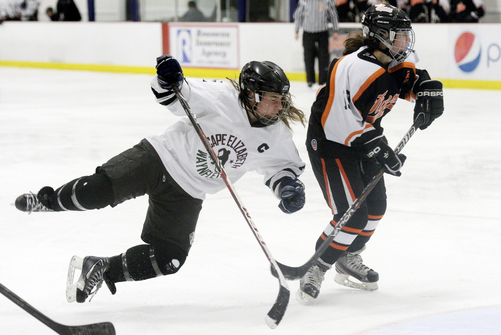 Julia Ginder of Cape Elizabeth/Waynflete heads to the ice after getting tangled with Mallory Mourmouras of Biddeford in front of the net.