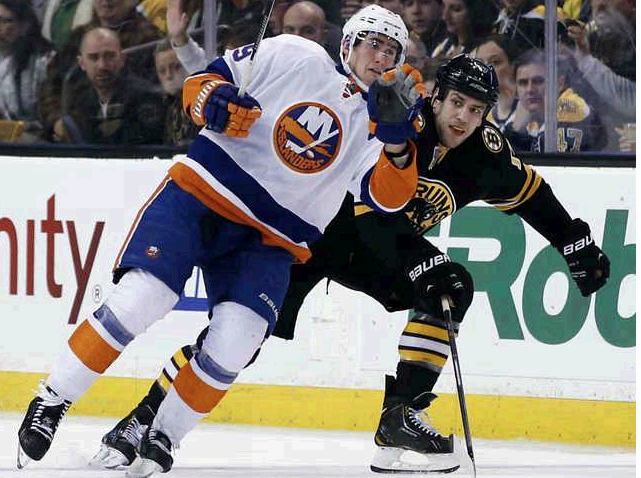 New York Islanders center Brock Nelson and Boston Bruins left wing Milan Lucic make contact as they skate down the ice during the third period in Boston on Tuesday.