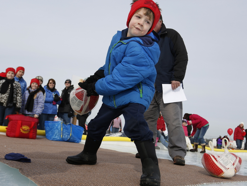 Ian House, 6, uses all his might to hurl a turkey during the turkey curling competition at the South Portland WinterFest. Onlooker watch his effort at the Wainwright Farms Recreation Complex on Saturday.