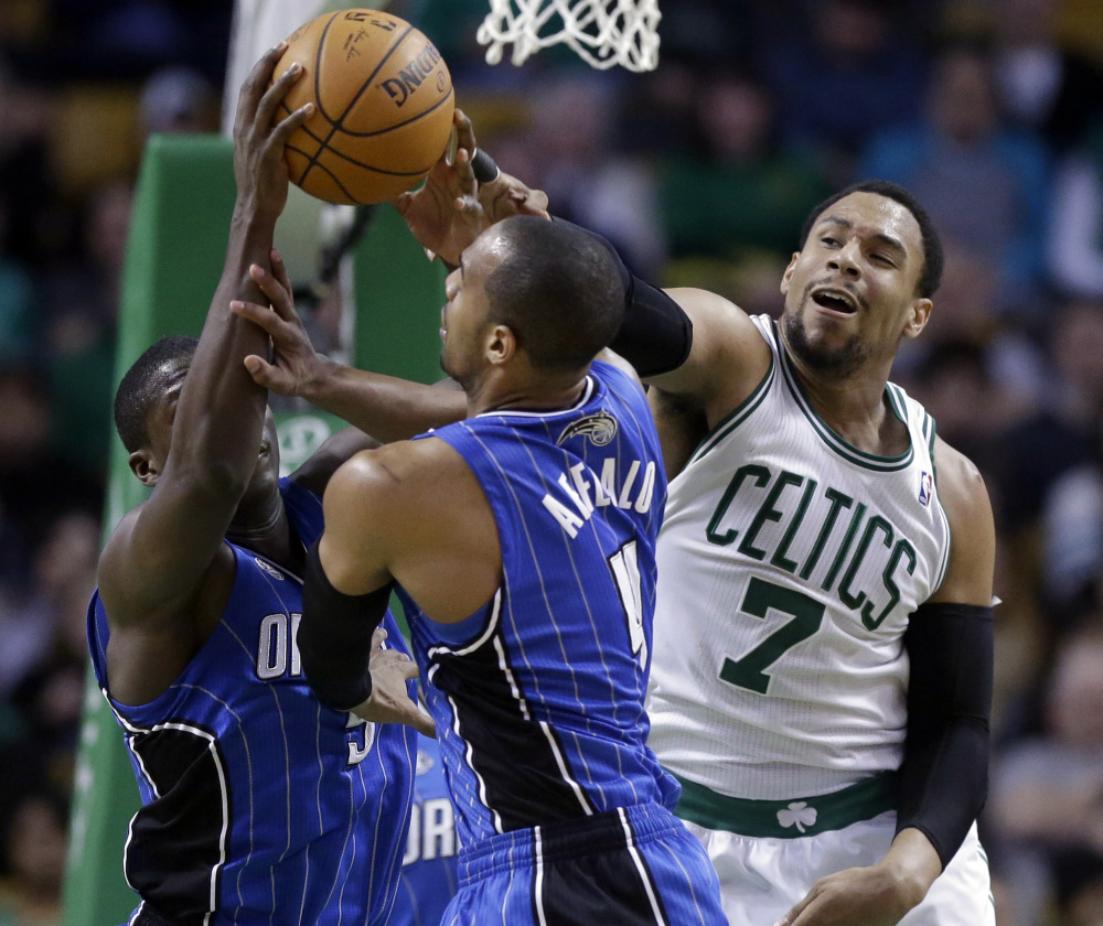 Celtics center Jared Sullinger, right, grapples with Magic guards Arron Afflalo, center, and Victor Oladipo during the third quarter of Boston's 96-89 win at home on Sunday.