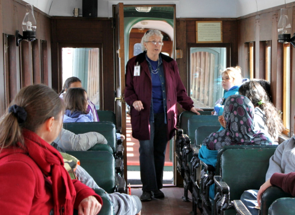 Docent Patricia Mahoney talks to a group of passengers aboard a Maine Narrow Gauge Railroad car. The Portland History Collaborative program has trained more than 700 volunteer guides that support affiliated historic organizations.