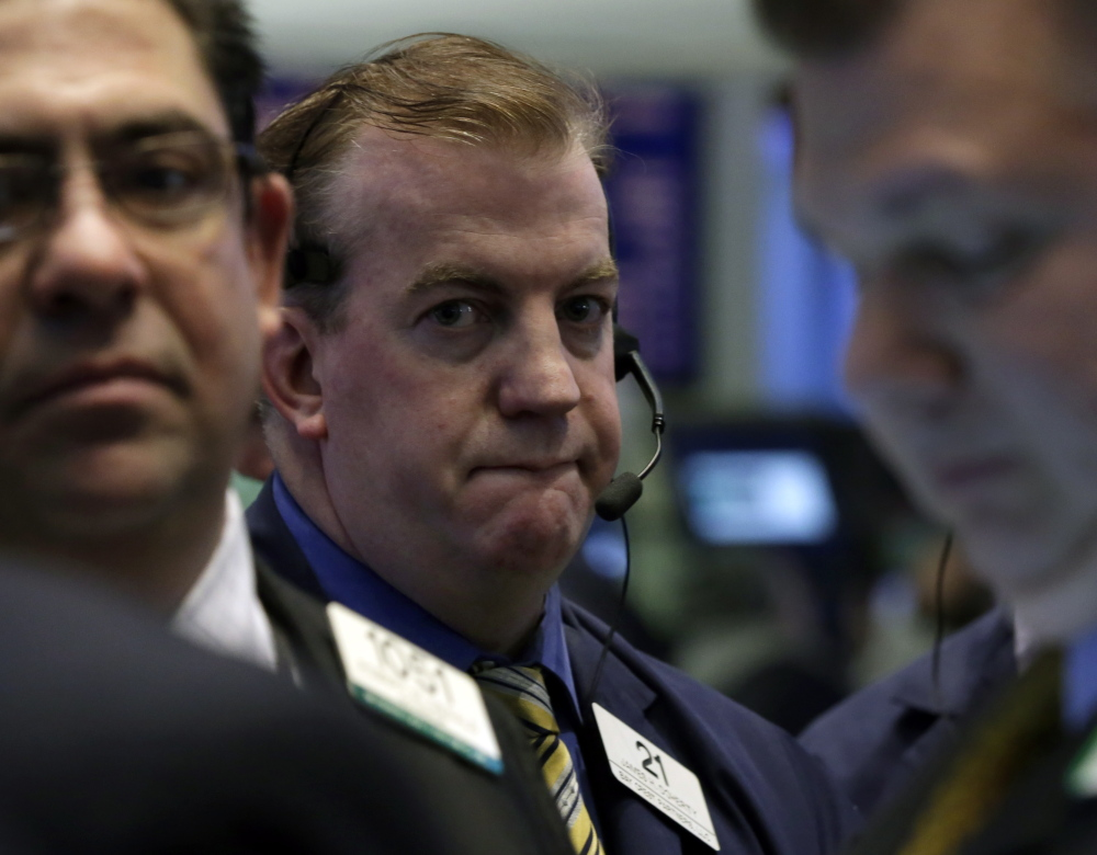 Traders work on the floor of the New York Stock Exchange on Friday, when markets ended the worst January since 2009.