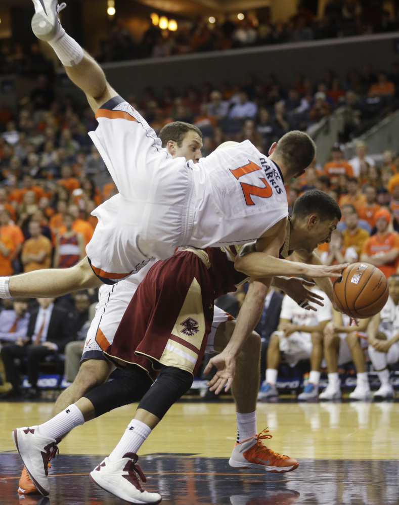 Virginia's Joe Harris heads to the floor as he and Boston College guard Lonnie Jackson go for a rebound in Wednesday night's game in Charlottesville, Va. Virginia won, 77-67.