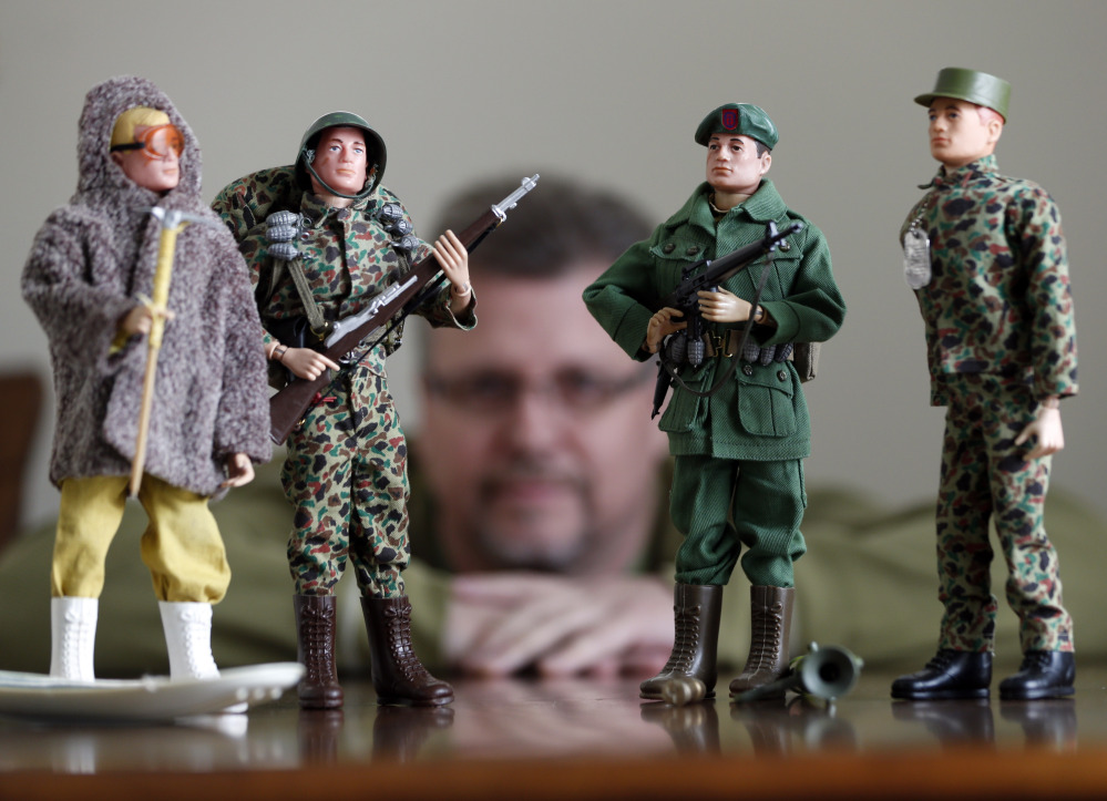 Tearle Ashby poses G.I. Joe action figures in Niskayuna, N.Y. A half-century after the 12-inch doll was introduced at a toy fair, the iconic action figure is being celebrated by collectors.
