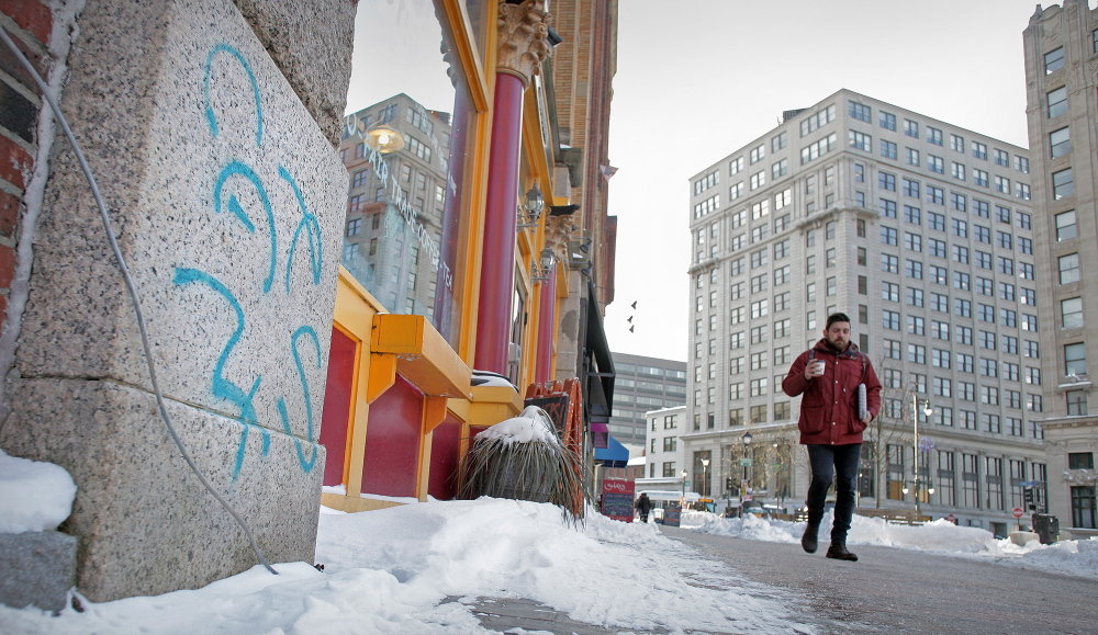 A pedestrian passes graffiti sprayed on the front of the Others! cafe in Portland's Monument Square. The graffiti problem appears to have magnified this winter, a time when the weather makes it difficult to wash away the unsightly vandalism.