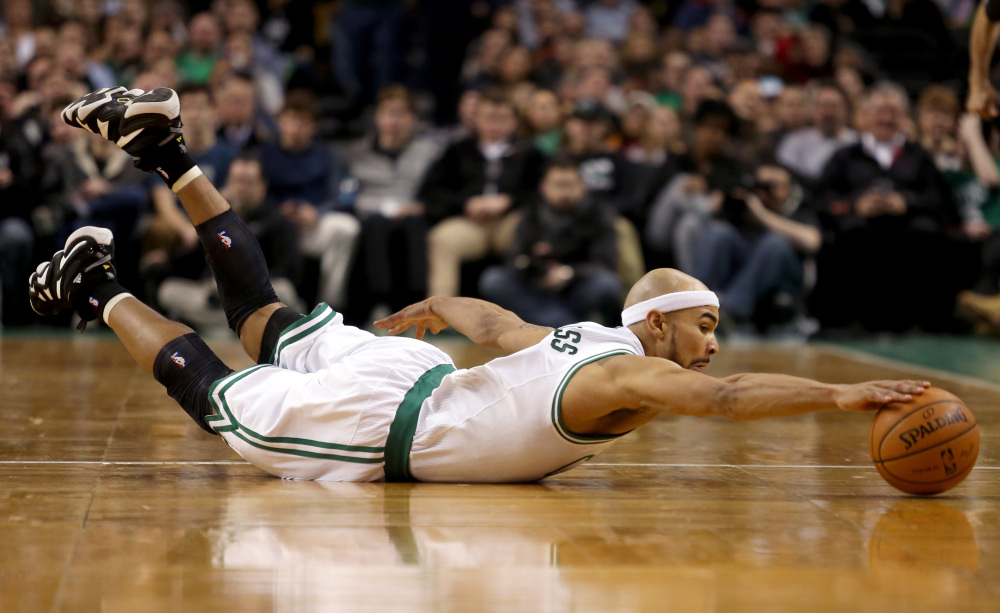Boston Celtics point guard Jerryd Bayless dives for a loose ball during the first half against the Sacramento Kings on Friday in Boston.
