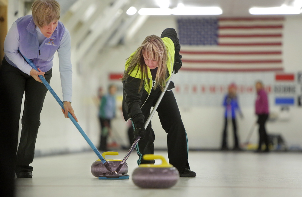 Tilly Atkins of Bath, left and Erica Sprague of Lincolnville sweep in front of a stone during a curling tournament at the Belfast Curling Club on Friday, January 17, 2014. The purpose of sweeping is to make the curling stone go farther.