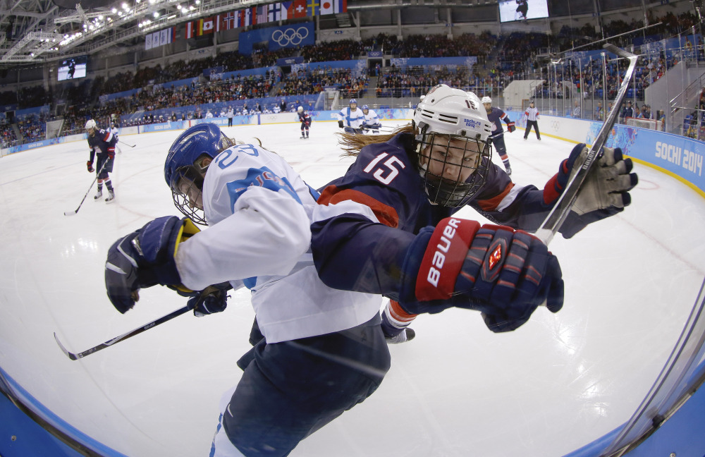 Nina Tikkinen of Finland and Anne Schleper of the United States battle for control of the puck against the glass during the second period of the women's hockey game at the Shayba Arena.