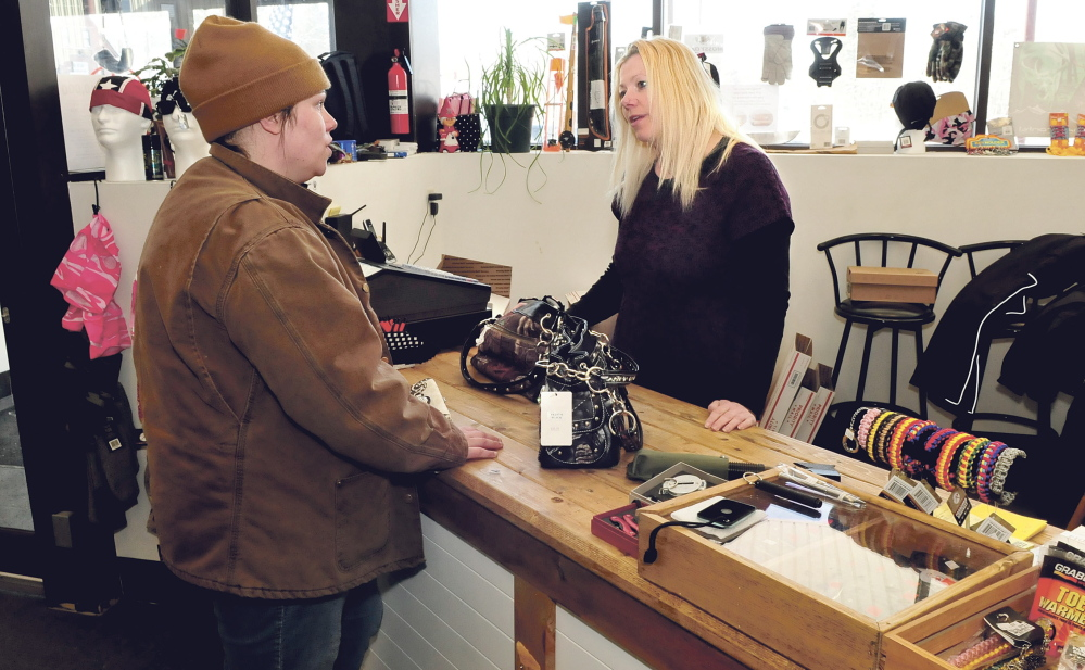 Bargain Hunter store owner Aimey Ribeiro, right, waits on customer Renee Reynolds at the Skowhegan business. The store carries everything from high-end dresses to ammo cans.