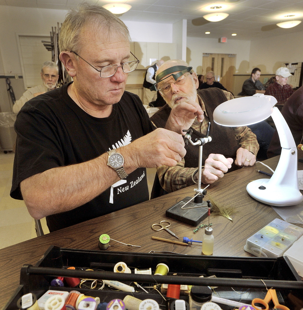 "Attentive to teacher, class participants Bob Harradon, left, of Yarmouth and Frank Miles of Cape Elizabeth tie their versions of Macauley Lord's ""ugly"" fly."