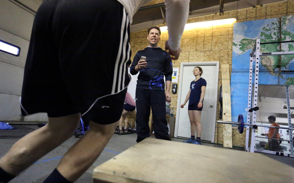 Will Sweetser, director of competitive programs at the Maine Winter Sports Center, leads athletes through a workout recently in a gym in Caribou. The center also has competition sites in Fort Kent and Presque Isle.