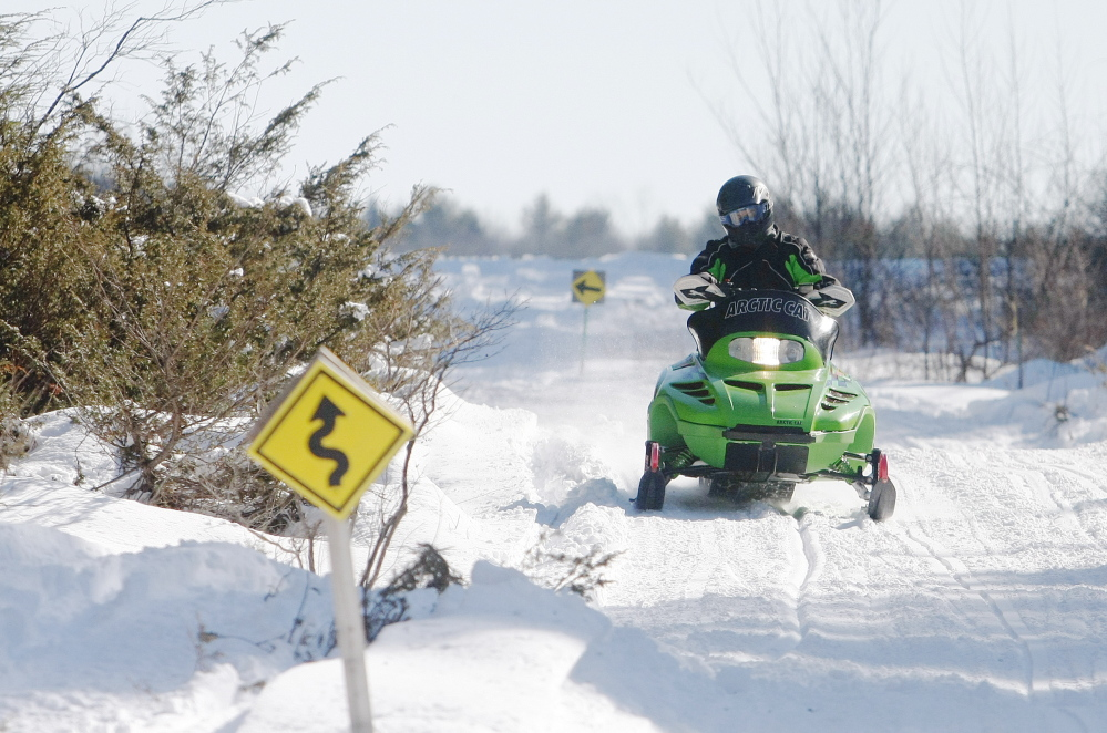 A snowmobiler winds along Route 89 – a section of the International Trail System – in Buxton on Sunday. Ideal conditions brought snowmobilers out on Maine trails, but at least 10 people were injured over the weekend.