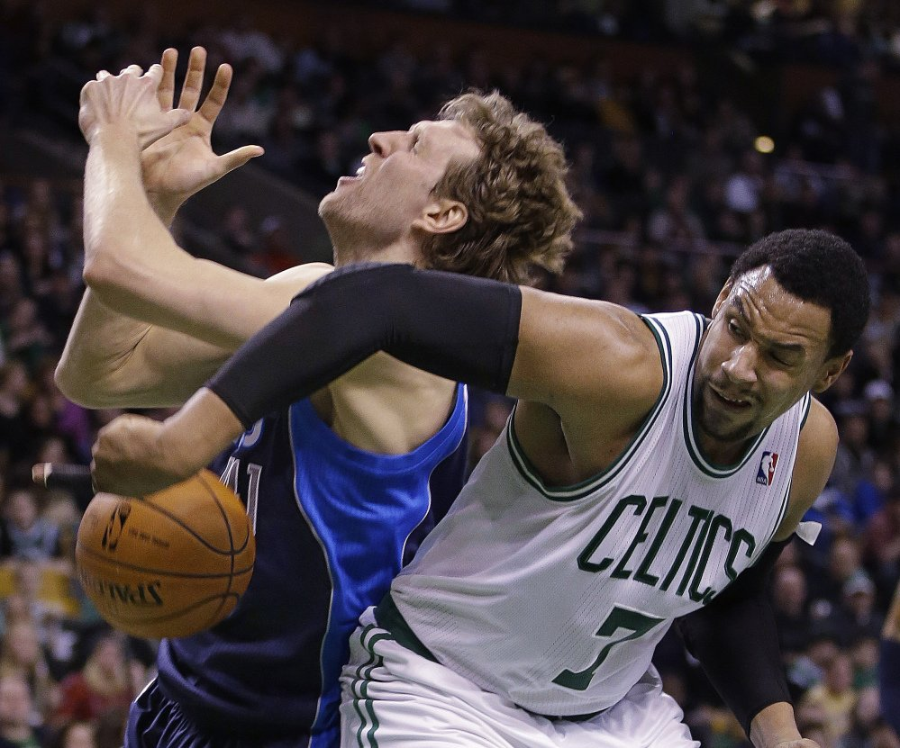 Celtics center Jared Sullinger, right, fouls Mavericks power forward Dirk Nowitzki going to the hoop during the second half of 102-91 Dallas win at Boston Sunday.