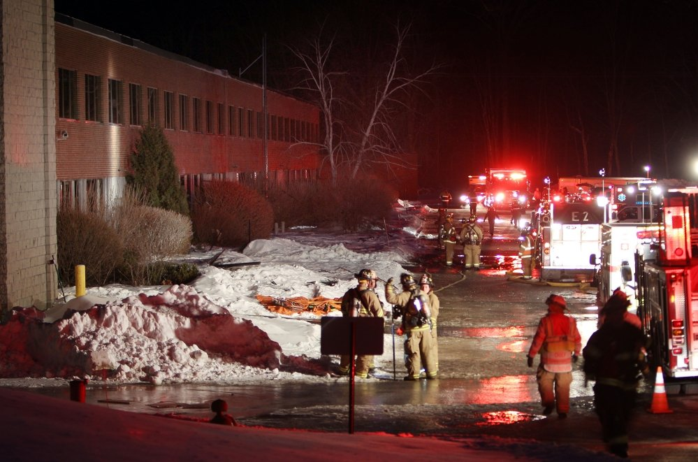 Emergency crews from several towns work outside the New Hampshire Ball Bearing plant after an explosion Monday in Peterborough, N.H.