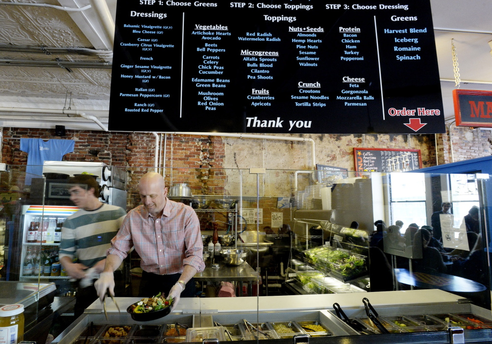 John Conzelman, owner of Daily Greens, composes a salad for a customer.