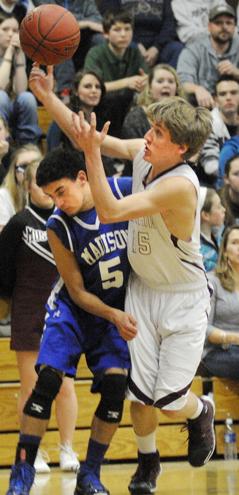 Staff photo by Andy Molloy HARD-FOUGHT AFFAIR: Monmouth Academy's Hunter Richardson, right, collects the ball while being guarded by Madison Area Memorial High School's Derek LeBlanc during a basketball match up Wednesday in Monmouth.