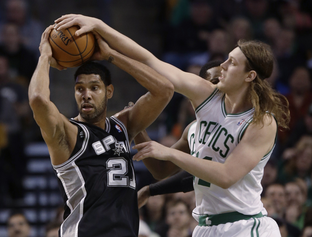 Boston Celtics center Kelly Olynyk, right, fouls San Antonio Spurs forward Tim Duncan as Duncan comes down with the rebound during the second half of an NBA basketball game in Boston on Wednesday.
