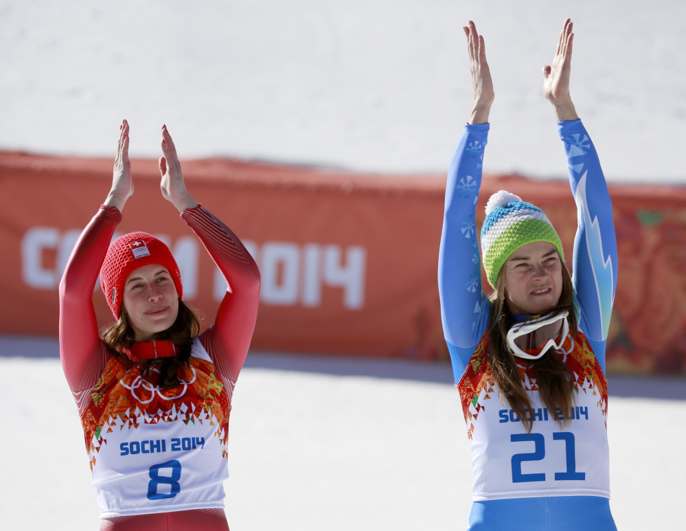 Women's downhill gold medalists Switzerland's Dominique Gisin, left, and Slovenia's Tina Maze, right, applaud during a flower ceremony at the Sochi 2014 Winter Olympics Wednesday.