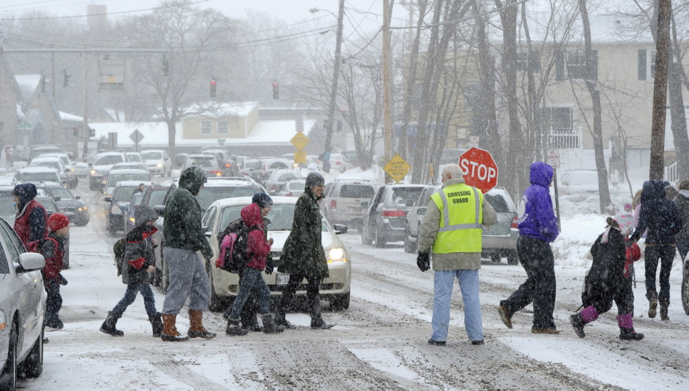 Crossing guide John Lewis stops traffic on Stevens Avenue in Portland as Longfellow Elementary School sends students home early Thursday because of the snowstorm.