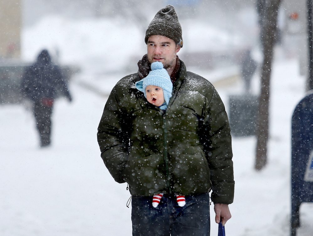 Russell Hoskins walks through the snow with his 5-month-old son, Evens, tucked into his jacket as they head down Congress Street to the Portland Public Library during Thursday's storm.