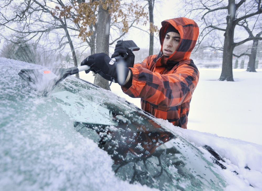 Mitchell Mamorsky, a University of New England Dental School student from Brooklyn, N.Y., scrapes ice Friday from his car, which he parked overnight in Portland's Deering Oaks.